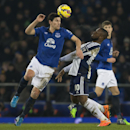 Everton's Gareth Barry, left, fights for the ball against West Bromwich Albion's Victor Anichebe during the English Premier League soccer match between Everton and West Bromwich Albion at Goodison Park Stadium, Liverpool, England, Monday Jan. 19, 2015