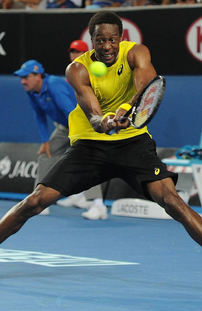 Gael Monfils of France makes a backhand return to Ryan Harrison of the U.S. during their first round match at the Australian Open tennis championship in Melbourne, Australia, Tuesday, Jan. 14, 2014