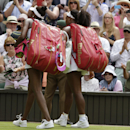 Serena Williams of the United States and Venus Williams of the United States walk off the court after their singles match, at the All England Lawn Tennis Championships in Wimbledon, London, Monday July 6, 2015. Serena Williams won 6-4, 6-3. (AP Photo/Alastair Grant)