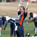 In this June 2, 2014 file photo, Denver Broncos quarterback Peyton Manning stretches during an NFL football organized team practice at the Broncos training facility in Englewood, Colo. After throwing for more yards and touchdowns than anyone in NFL histor