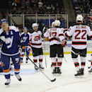New Jersey Devils' Adam Henrique (14) celebrates his goal with teammates as New York Islanders' Kyle Okposo, left foreground, skates away in the first period of an NHL hockey game on Saturday, March 1, 2014, in Uniondale, N.Y The Associated Press