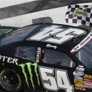Kyle Busch (54) waves the checkered flag after winning the NASCAR Nationwide Series auto race at the Charlotte Motor Speedway in Concord, N.C., Saturday, May 25, 2013. (AP Photo/Gerry Broome)
