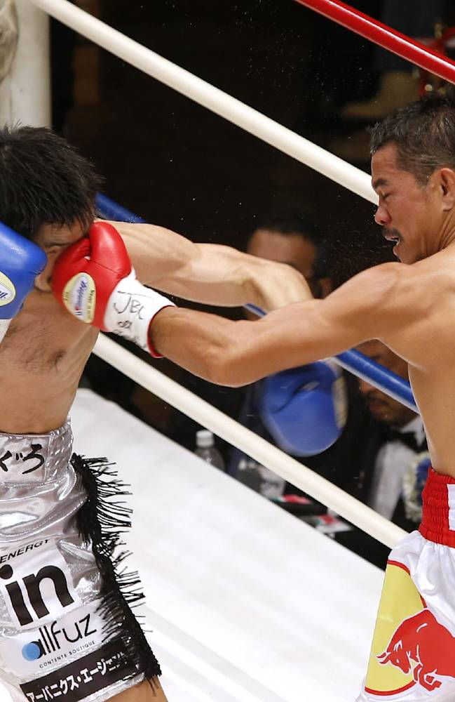 Thailand's Denkaosen Kaovichit, right, lands a left on the face of Japan's Kohei Kono in the third round of their boxing match for the vacant WBA World super flyweight title in Tokyo, Wednesday, March 26, 2014. Kono knocked out Denkaosen in the eighth round to clinch the title