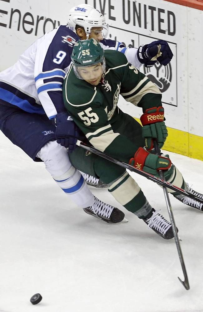 Winnipeg Jets' Evander Kane (9) attempts to slow down Minnesota Wild's Mathew Dumba (55) who races around the net for the puck in the first period of an NHL hockey game on Thursday, Oct. 10, 2013, in St. Paul, Minn
