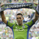 FILE - In this Aug. 3, 2013 file photo, Clint Dempsey raises a Seattle Sounders scarf during a ceremony to introduce him as the newest member of the team, prior to a MLS soccer match between the Sounders and FC Dallas in Seattle. Dempsey was blown away by the reception he received the night he was introduced as the Seattle Sounders newest designated player. On Sunday night, Aug. 25, 2013, he's expected to make his home debut before 67,000 fans against rival Portland. (AP Photo/Ted S. Warren, File)