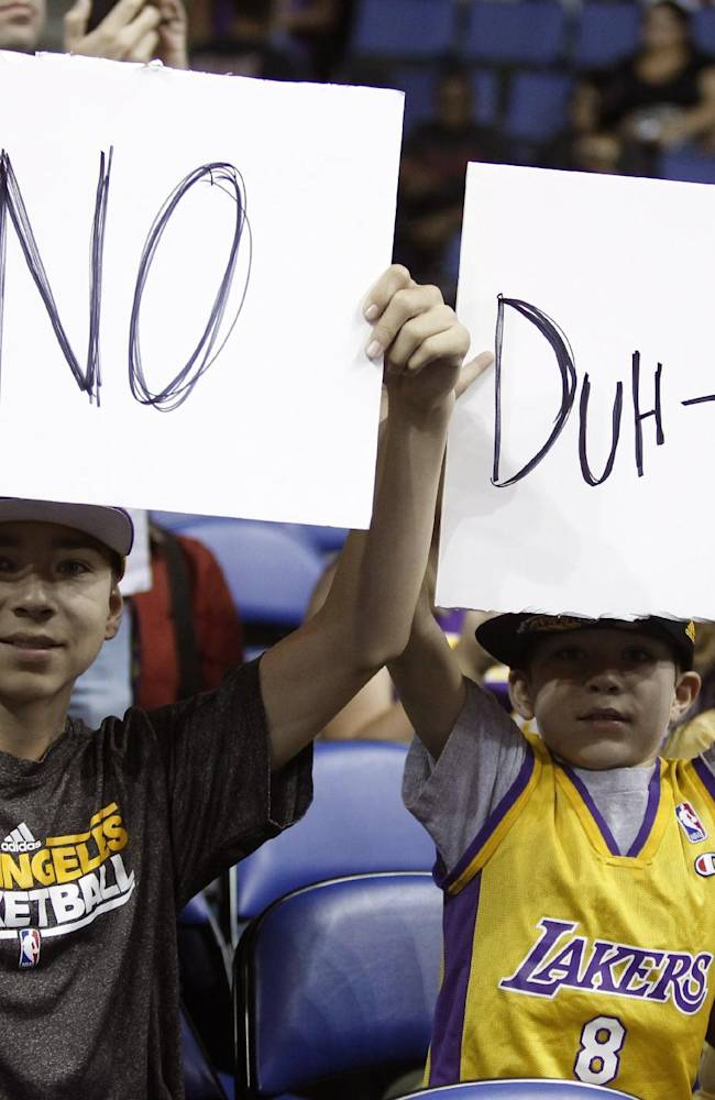 Los Angeles Lakers fans 12-year-old Ian Klock and his 9-year-old brother Nate Klock, both from Upland, Calif., display posters about Dwight Howard, prior to the Lakers' NBA basketball preseason game against the Golden State Warriors on Saturday, Oct. 5, 2013, in Ontario, Calif