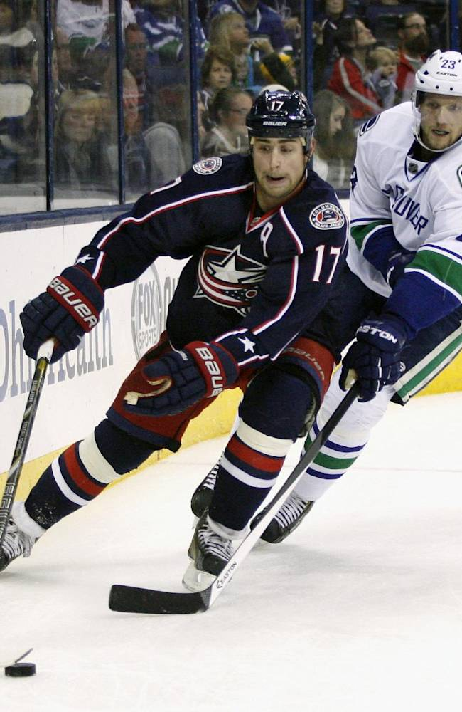 Columbus' Brandon Dubinsky (17) skates away from Vancouver's Alexander Edler during the second period of an NHL hockey game Sunday, Oct. 20, 2013, in Columbus, Ohio