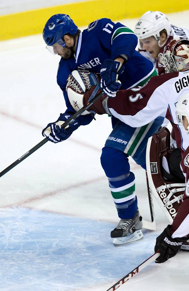 Vancouver Canucks' Ryan Kesler, left, scores a goal as Colorado Avalanche's Gabriel Landeskog, top right, of Sweden, goalie Jean-Sebastien Giguere and Andre Benoit, bottom right, watch during third period of an NHL hockey game in Vancouver, British Columbia, on Sunday, Dec. 8, 2013
