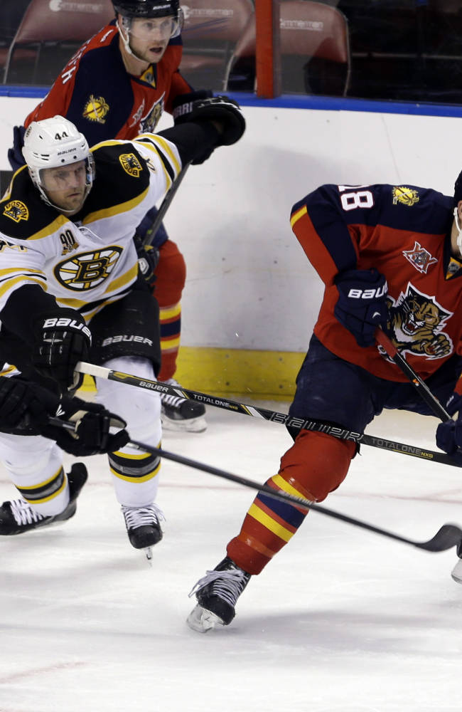 Boston Bruins left wing Loui Eriksson (21) and Dennis Seidenberg (44) check Florida Panthers center Shawn Matthias (18) in the third period of an NHL hockey  game, Thursday, Oct. 17, 2013, in Sunrise, Fla. The Bruins won 3-2