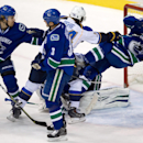 St. Louis Blues' T.J. Oshie,checks Vancouver Canucks' Ryan Stanton, right, over goalie goalie Eddie Lack, of Sweden, as David Booth, left, and Kevin Bieksa defend during the first period of an NHL hockey game in Vancouver, British Columbia, on Wednesday,