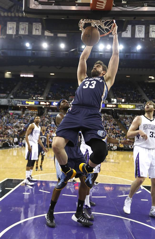 Memphis Grizzlies center Marc Gasol, of Spain, hangs on the rim after stuffing against  Sacramento Kings center Aaron Gray, right,  during the first quarter of an NBA basketball game in Sacramento, Calif., Wednesday, Jan. 29, 2014
