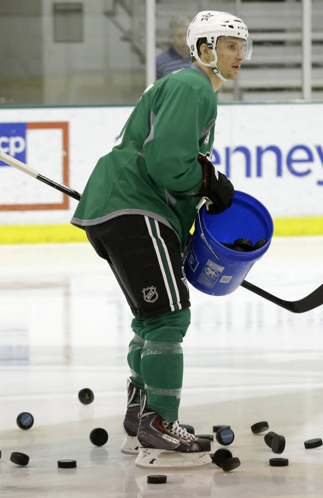 Dallas Stars left wing Antoine Roussel (21) dumps a bucket of pucks on the ice during NHL hockey training camp Thursday, Sept. 19, 2013, in Frisco, Texas