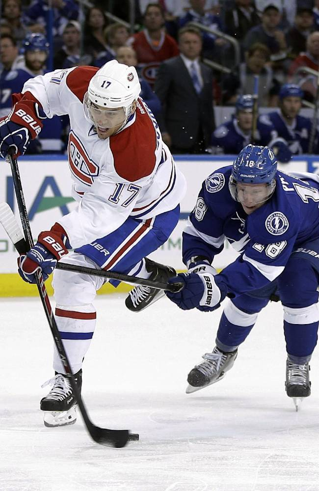 Tampa Bay Lightning left wing Ondrej Palat. right, of the Czech Republic, hooks Montreal Canadiens left wing Rene Bourque (17) as Bourque goes in on a breakaway during the first period of an NHL hockey game Tuesday, April 1, 2014, in Tampa, Fla