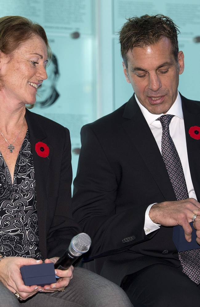 Hockey Hall of Fame inductees Geraldine Heaney and Chris Chelios inspect their rings after being presented with them  at the Hall in Toronto on Friday, Nov. 8, 2013