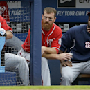 Washington Nationals' Adam LaRoche, left, and teammate Denard Span, right, look out from the dugout after LaRoche hit a home run in the ninth inning of a baseball game against the Atlanta Braves, Sunday, April 13, 2014, in Atlanta. The Braves won 10-2 The