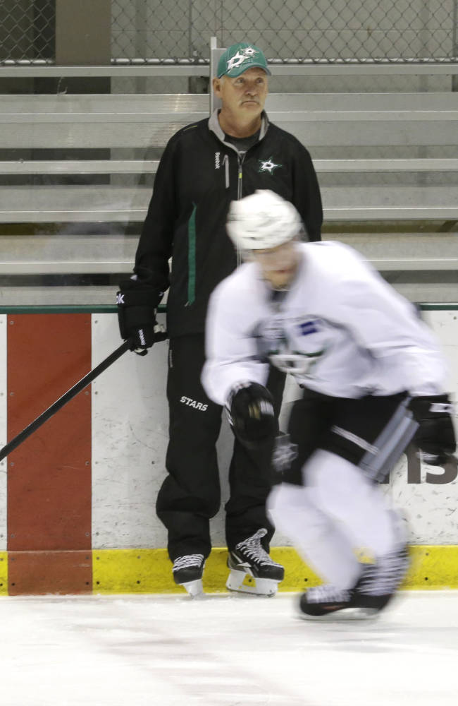 Dallas Stars head coach Lindy Ruff  watches from the boards during NHL hockey training camp Thursday, Sept. 19, 2013, in Frisco, Texas