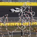 Carl Edwards takes his car through Turn 3 past a holiday light display during NASCAR Sprint Cup testing for the 2014 season at Charlotte Motor Speedway in Concord, N.C., Wednesday, Dec. 11, 2013. (AP Photo/Chuck Burton)