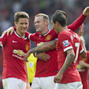 Manchester United's Wayne Rooney, centre, celebrates with teammates after scoring against Queens Park Rangers during their English Premier League soccer match at Old Trafford Stadium, Manchester, England, Sunday Sept. 14, 2014