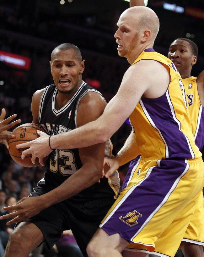 San Antonio Spurs forward Boris Diaw, left, of France, secures the ball as Los Angeles Lakers center Chris Kaman, front right, attempts to steal with Lakers guard Wesley Johnson, back right, looking on during an NBA basketball game on Friday, Nov. 1, 2013, in Los Angeles. The Spurs won 91-85