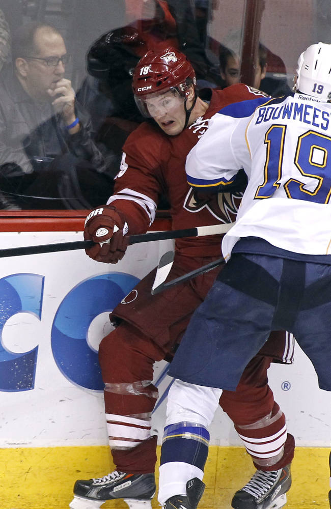 Phoenix Coyotes' Shane Doan, left, is checked into the boards by St Louis Blues' Jay Bouwmeester (19) during the second period of an NHL hockey game on Sunday, March 2, 2014, in Glendale, Ariz