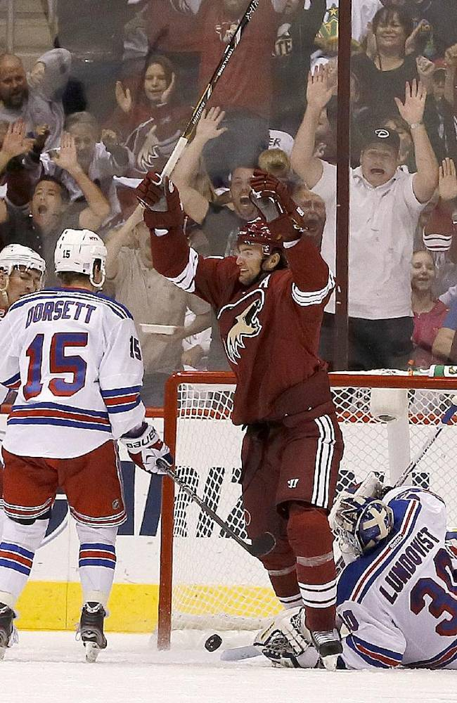Phoenix Coyotes' Martin Hanzal, of the Czech Republic, celebrates along with teammate Antoine Vermette, right, on a goal scored by Coyotes' Radim Vrbata, of the Czech Republic, against New York Rangers' Henrik Lundqvist (30), of Sweden, as Rangers' Derek Dorsett (15), John Moore (17), and Ryan McDonagh, second from left, arrive late to defend in the second period during an NHL hockey game on Thursday, Oct. 3, 2013, in Glendale, Ariz