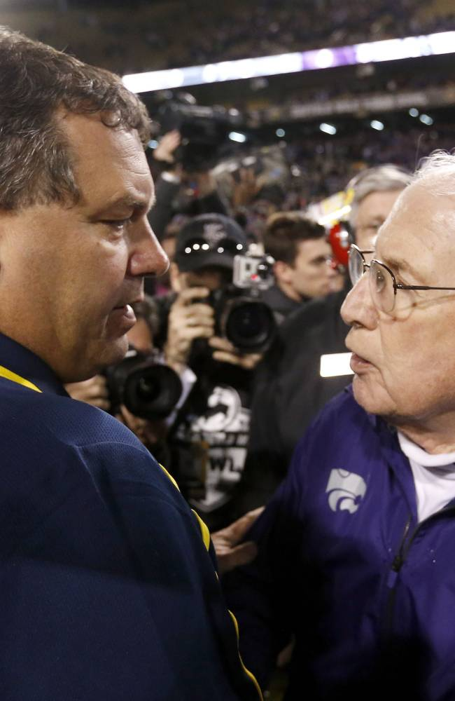 Kansas State head coach Bill Snyder, right, meets with Michigan head coach Brady Hoke as the two talk on the field after the Buffalo Wild Wings Bowl NCAA college football game Saturday, Dec. 28, 2013, in Tempe, Ariz.  Kansas State defeated Michigan 31-14