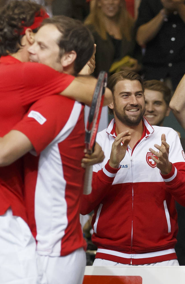 Roger Federer, 2nd left, of Switzerland, celebtrates with Swiss Davis Cup Team captain Severin Luethi, in front of teammates Marco Chiudinelli, left, Michael Lammer, 2nd right, and Stanislas Wawrinka, right, after winning against Italy, during  the Davis Cup World Group Semifinal between Switzerland and Italy in Geneva, Switzerland, Sunday, Sept. 14, 2014.  Roger Federer has taken Switzerland to its first Davis Cup final in 22 years, beating Fabio Fognini of Italy in the opening reverse singles Sunday for a winning 3-1 lead in their semifinal.  Switzerland will play at France in the final on Nov. 21-23. The French beat two-time defending champion Czech Republic this weekend