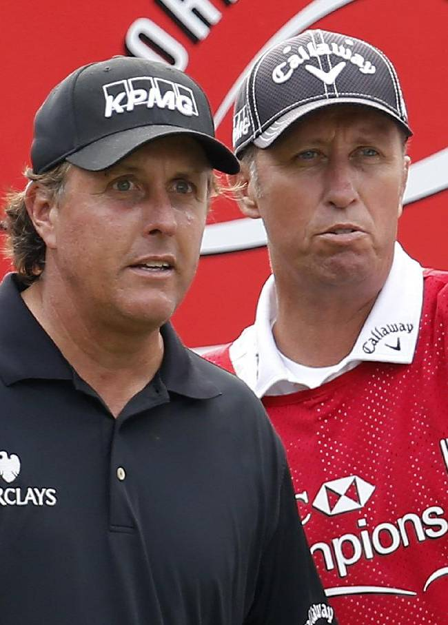 Phil Mickelson of the United States, left, listens to his caddie before tying off the 10th hole during the second round of the HSBC Champions golf tournament at the Sheshan International Golf Club in Shanghai, China, Friday, Nov. 1, 2013