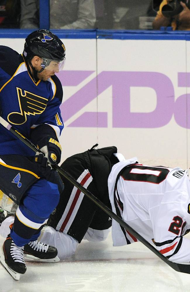 St. Louis Blues' Derek Roy, left, and Chicago Blackhawks' Brandon Saad reach for a loose puck during the second period of an NHL hockey game Wednesday, Oct. 9, 2013, in St. Louis