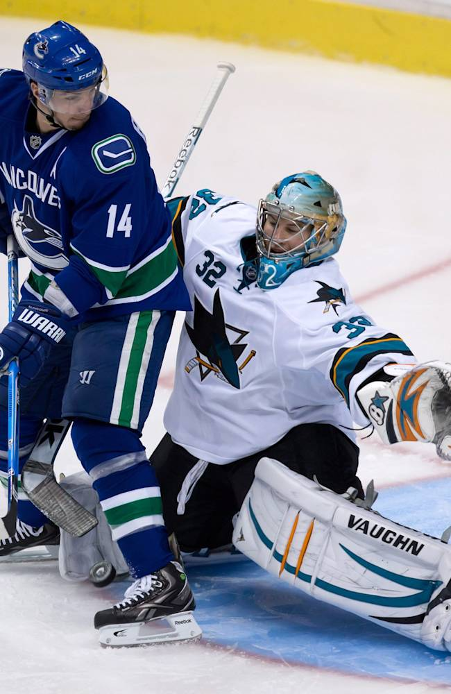 San Jose Sharks' goalie Alex Stalock, right, of Finland, makes the save while being screened by Vancouver Canucks' Alex Burrows during second period pre-season NHL hockey action in Vancouver, British Columbia on Monday Sept. 16, 2013