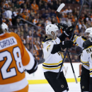 From right to left, Boston Bruins' Brad Marchand, Andrej Meszaros, of Slovakia, and Dougie Hamilton celebrate after Meszaros' goal as Philadelphia Flyers' Claude Giroux skates by during the first period of an NHL hockey game on Sunday, March 30, 2014, in
