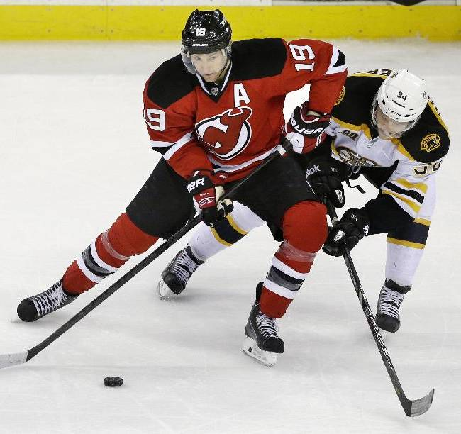Boston Bruins' Carl Soderberg (34), of Sweden, and New Jersey Devils' Travis Zajac (19) battle over the puck during during the third period of an NHL hockey game in Newark, N.J., Sunday, April 13, 2014. The Devils won 3-2
