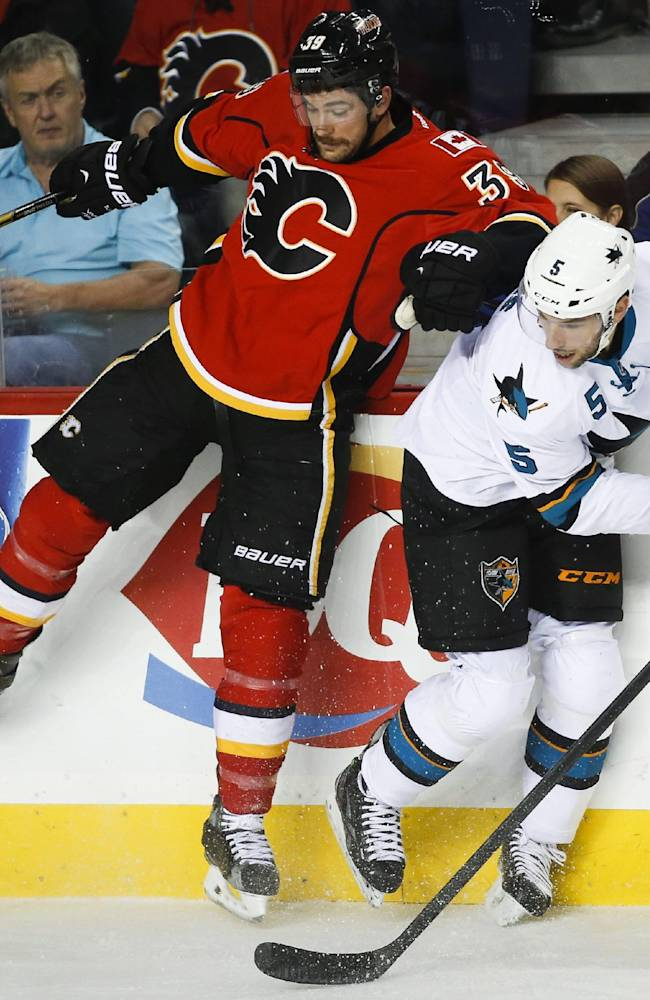 San Jose Sharks' Jason Demers, right, dodges a check from Calgary Flames' TJ Galiardi during the first period of an NHL hockey game Tuesday, Nov. 12, 2013, in Calgary, Alberta