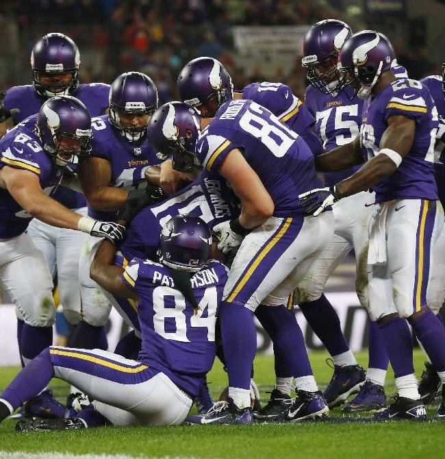 Minnesota Vikings wide receiver Greg Jennings (15) is swarmed by his teammates after scoring on a 16-yard touchdown pass from quarterback Matt Cassel during the second half of their NFL football game at Wembley Stadium, London, Sunday,Sept. 29, 2013