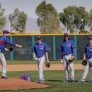 Chicago Cubs pitcher Justin Grimm, left, runs pick off drills as pitchers Kyle Kendricks, Jeff Samardzija and Travis Wood watch during the team's first spring training baseball practice, Friday, Feb. 14, 2014, in Mesa, Ariz The Associated Press