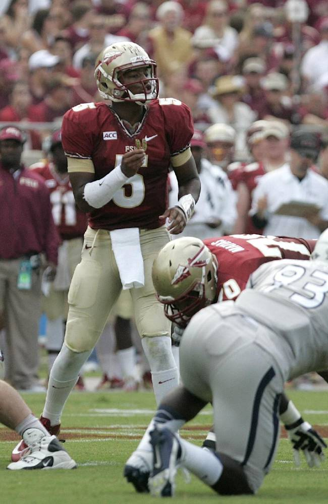 In this Saturday, Sept. 14, 2013, file photo, Florida State's Jameis Winston, center, calls signals as he checks the defense of Nevada during an NCAA college football game in Tallahassee, Fla. The Seminoles scored five offensive touchdowns during an 8:15 span in the 62-7 rout against Nevada. That was impressive, but coach Jimbo Fisher believes the unit can move faster