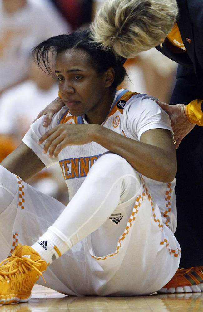 In this Jan. 23, 2014, file photo, Tennessee guard Ariel Massengale (5) is assisted by head coach Holly Warlick after getting injured in the first half of an NCAA college basketball game in Knoxville, Tenn. Massengale missed the final 16 games of the 2013-14 season because of a head injury