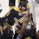 Boston Bruins center Patrice Bergeron, right,  is embraced by teammate Zdeno Chara, left,  after scoring the game winning goa