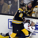 Boston Bruins left wing Justin Florek (57) checks Washington Capitals defenseman Mike Green into the boards during the third period of an NHL preseason hockey game in Boston, Wednesday, Sept, 24, 2014. The Bruins won 2-0. The Associated Press