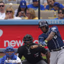 San Diego Padres' Justin Upton, right, hits a grand slam while Los Angeles Dodgers catcher Austin Barnes, left, and home plate umpire Alan Porter watch during the first inning of a baseball game, Sunday, May 24, 2015, in Los Angeles. (AP Photo/Mark J. Terrill)