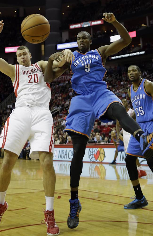 Houston Rockets' Donatas Motiejunas (20) and Oklahoma City Thunder's Serge Ibaka (9) battle for a loose ball during the third quarter of an NBA basketball game Thursday, Jan. 16, 2014, in Houston. The Thunder beat the Rockets 104-92