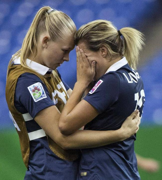 France's Claire Lavogez, right, is consoled by teammate Charlotte Saint Sans after the team's 2-1 loss to Germany in a FIFA U-20 women's World Cup semifinal in Montreal on Wednesday, Aug. 20, 2014