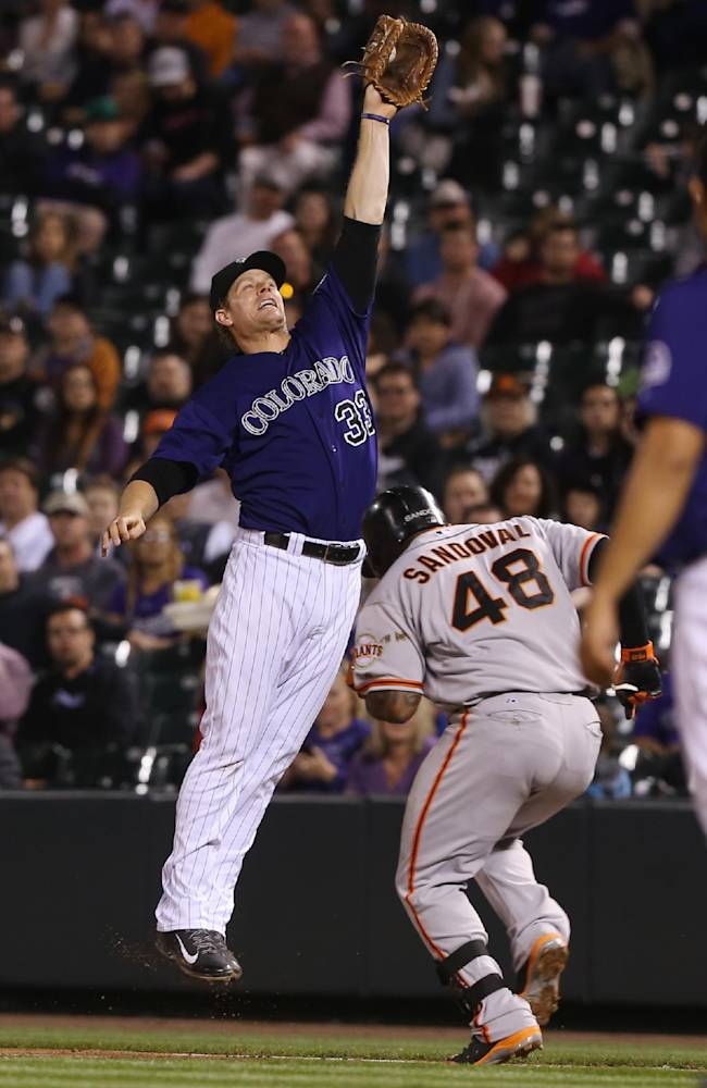 Colorado Rockies first baseman Justin Morneau, left, fields the throw as San Francisco Giants' Pablo Sandoval reaches first base on an infield single in the fourth inning of a baseball game in Denver on Monday, April 21, 2014
