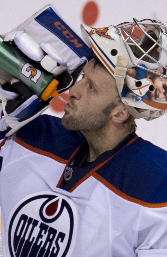 Edmonton Oilers goalie Jason LaBarbera (1) takes a drink of water during the third period of NHL hockey action against the Vancouver Canucks in Vancouver, British Columbia, Saturday, Oct. 5, 2013
