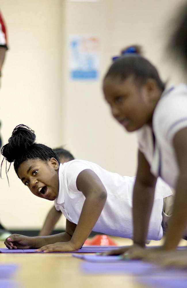 M. Agnes Jones Elementary School fifth grader Yakia Edmonds, center, does push-ups with classmates as Atlanta Falcons' Harland Gunn, standing at rear left, runs a drill as the NFL football team takes part in the volunteer project,