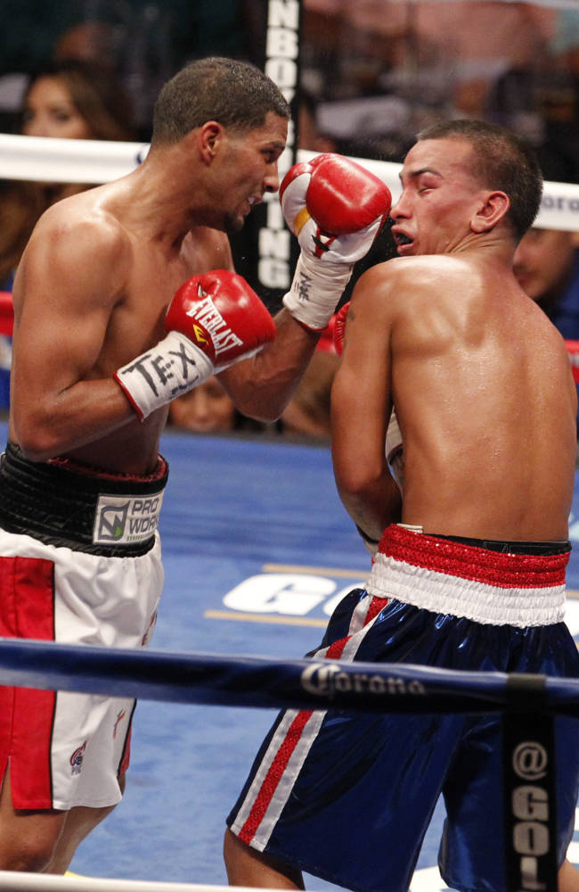 Jerry Belmontes, right, takes a blow from Abner Cotto, of Puerto Rico, during a boxing match Thursday, Aug. 7, 2014, in Corpus Christi, Texas. Cotto won by a split decision