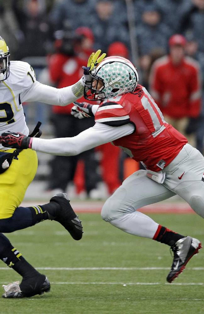 In this Nov. 24, 2012 file photo, Michigan quarterback Devin Gardner, left, escapes a tackle from Ohio State linebacker Ryan Shazier during an NCAA college football game in Columbus, Ohio. A year ago, Ohio State's coaches were driven to distraction by defenders unable to wrap up and make a stop in the open field. Even though the fourth-ranked Buckeyes still aren't perfect in that regard, they feel they've made remarkable improvement from 2012