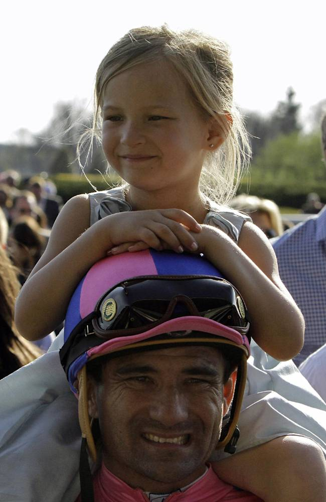 Lilah Nakatani rides on the shoulders of her father, Corey Nakatani, as they leave the track following Corey's victory aboard Dance With Fate in the Blue Grass Stakes horse race at Keeneland in Lexington, Ky., Saturday, April 12, 2014