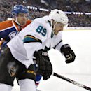 San Jose Sharks' Barclay Goodrow (89) and Edmonton Oilers' Andrew Ference (21) battle in the corner during first period of an NHL hockey game in Edmonton, Alberta, Sunday Dec 7, 2014 The Associated Press