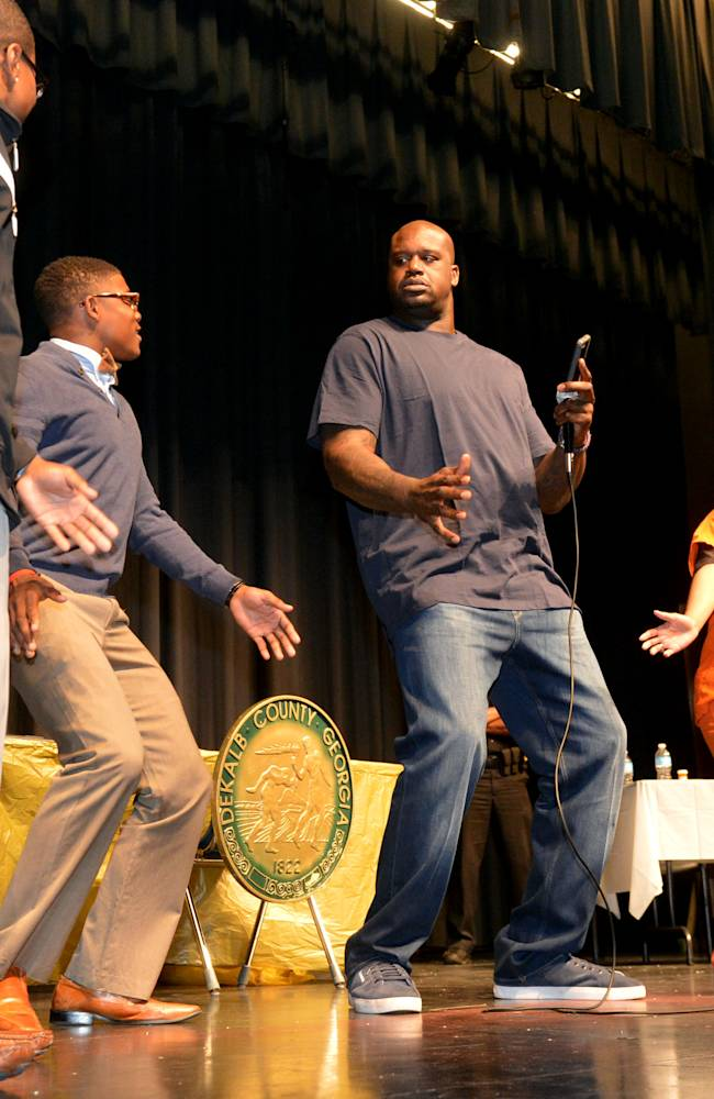 Arabia Mountain seniors, from left to right, Demetro Stevens, Greg Phillips and Alexis Smoot dance with retired NBA basketball player Shaquille O'Neal, second from right, during an educational program highlighting the impact of dangerous driving practices and distracted driving on Thursday, April 3, 2014, in Lithonia, Ga
